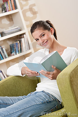 Students - Happy teenager with book on armchair