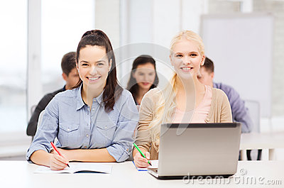 Students with laptop and notebooks at school
