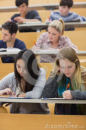 Students learning in a lecture hall with one girl using tablet pc