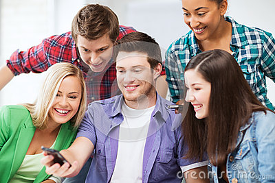 Students looking into smartphone at school