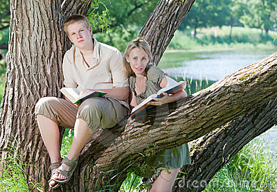 Students read books on the bank of lake