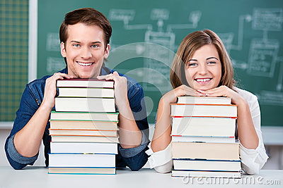 Students Resting Chin On Stack Of Books At Desk