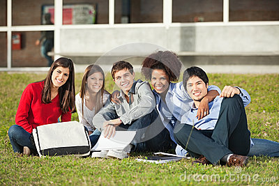 Students Sitting On Grass At College Campus