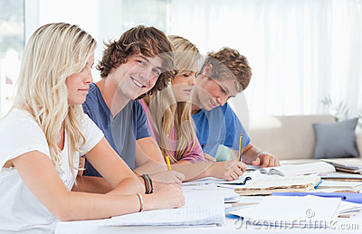 Students studying together with one man looking at the camera