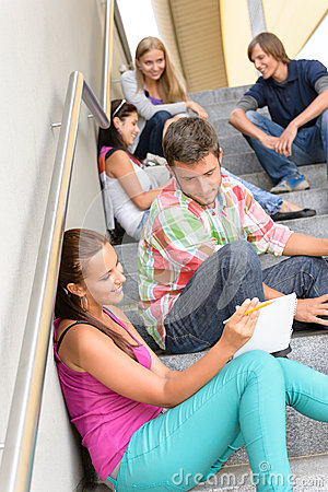 Students talking relaxing on school steps teens