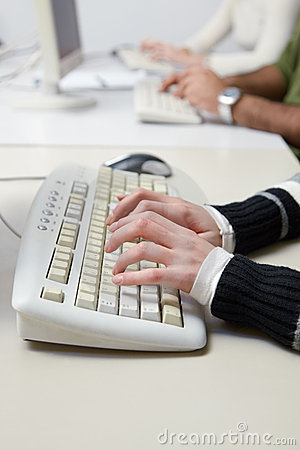 Students typing on keyboard in computer class