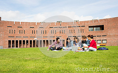Students using laptop in lawn against college building