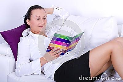 Studerande bok för attraktiv brunett på den vita soffan