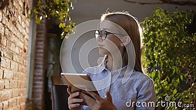 Studie-, affärs-, folk-, finans- och redovisningsbegrepp Den härliga unga flickan med långt hår i exponeringsglas arbetar på lager videofilmer