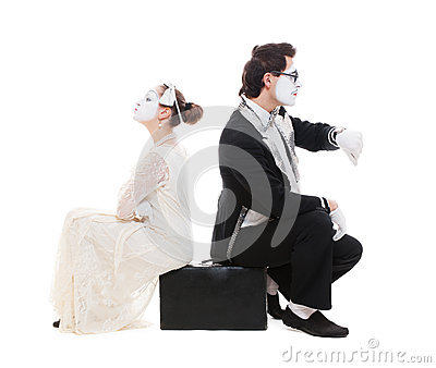 Studio picture of two mimes sitting on suitcase