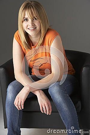 Studio Portrait Of Teenage Girl Sitting In Chair