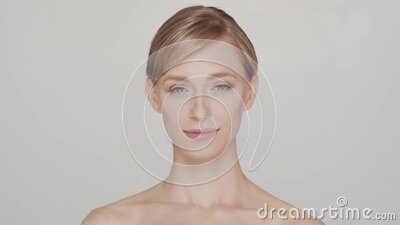 Studio portrait of young and beautiful woman over grey background stock footage