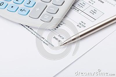 Studio shot of calculator and pen over some receipt