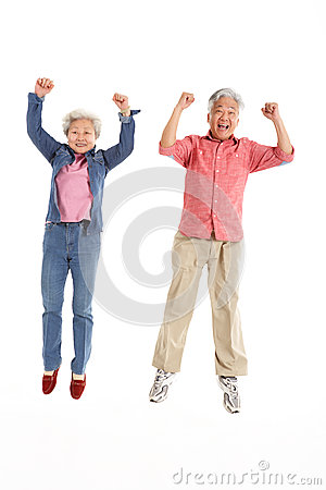 Studio Shot Of Chinese Senior Couple Jumping