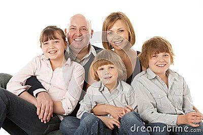 Studio Shot Of Family Group Sitting In Studio