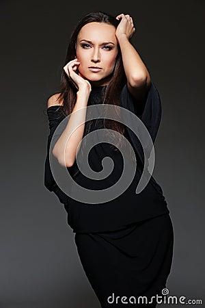 Studio shot of graceful young woman over dark