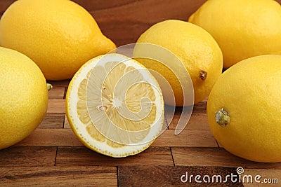 Studio shot of lemons on wooden pad