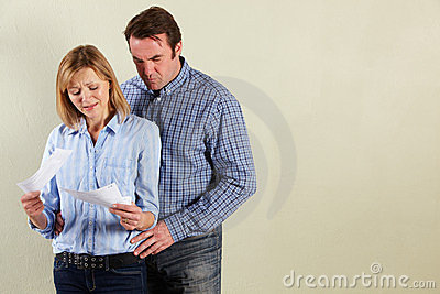 Studio Shot Of Middle Aged Couple Looking at Bills
