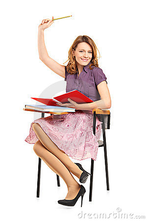 A studio shot of a schoolgirl raising her hand