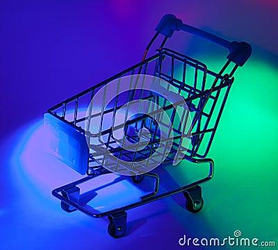 Studio shot of shopping cart in multicolor light