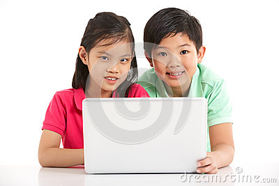 Studio Shot Of Two Chinese Children With Laptop