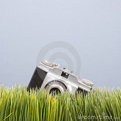 Studio shot of vintage camera in grass.