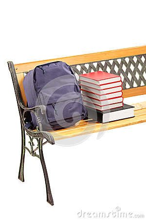 Studio shot of a wooden bench with books and school bag on it