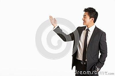 Studiostående av kinesiskt göra en gest för affärsman
