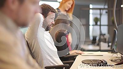 Stufato di lavoro giovanile che si allunga durante il duro lavoro su un computer in ufficio video d archivio