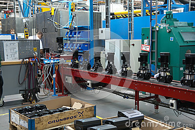 Stuff at conveyor with fabricated pumps on a plant Editorial Stock Photo