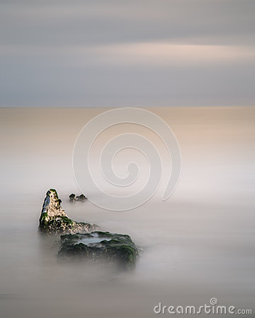 Stunning minimal long exposure landscape of rocks in ocean