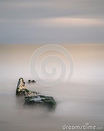 Stunning minimal long exposure landscape of rocks in ocean
