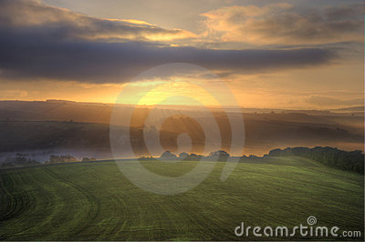 Stunning sunrise over fields landscape