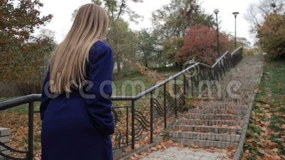 Stunning woman climbing staircase in autumn park stock video