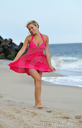 Stunning young blonde woman walking on the beach