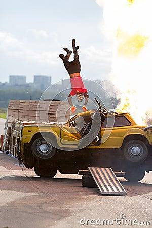 Stuntman flies over the burning car Editorial Image