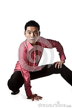 Stylish asian young man squatting