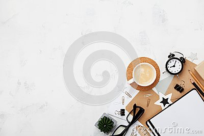 Stylish blogger working desk with coffee, office supply, alarm clock and clean notebook on white table top view. Flat lay. Stock Photo