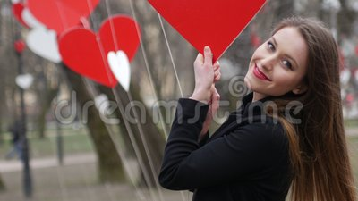 Stylish blonde girl cheerfully smiling and playing with red paper hearts decoration in the autumn park. Valentine's day stock footage