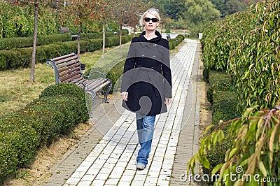 Stylish blonde woman walking in  in park