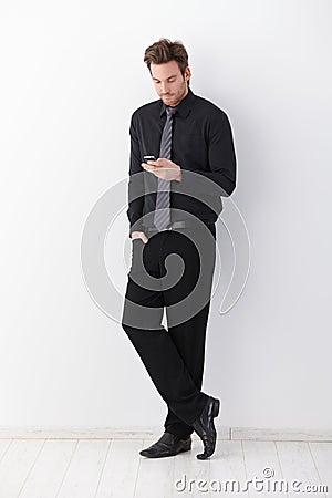 Stylish businessman writing text message