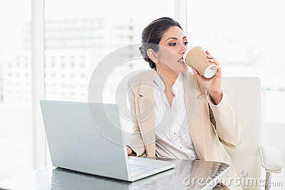 Stylish businesswoman drinking coffee while working on laptop