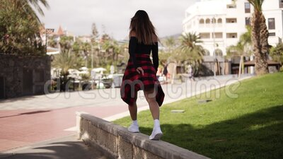 Stylish girl is stepping by parapet, balancing. Fashionable tourist in casual clothes walking along the tropical trees. Park, resort area on parapet. Elegant stock video footage