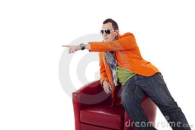 Stylish guy with glasses sitting on a red chair