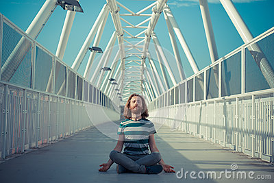 Stylish hipster model with long red hair and beard yoga