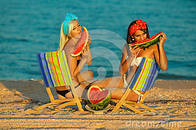 Stylish ladies at sea with watermelon