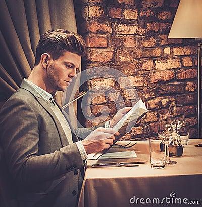 Stylish wealthy man with menu