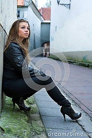 Stylish woman leaning on wall