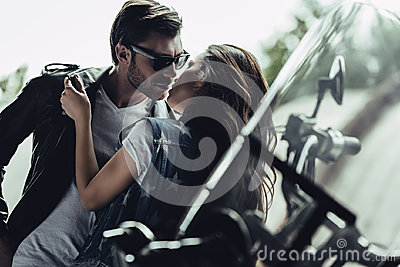 Stylish young couple hugging and kissing on motorcycle outdoors Stock Photo