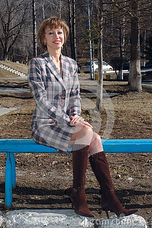 Stylish young woman sit on the bench.